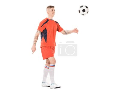 full length view of smiling young soccer player kicking ball isolated on white