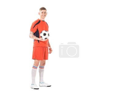 full length view of handsome young soccer player holding ball and smiling at camera isolated on white
