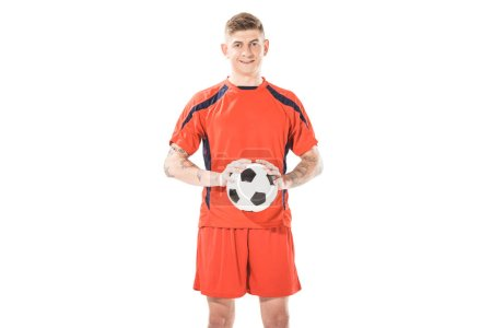 Photo for Handsome young soccer player holding ball and smiling at camera isolated on white - Royalty Free Image