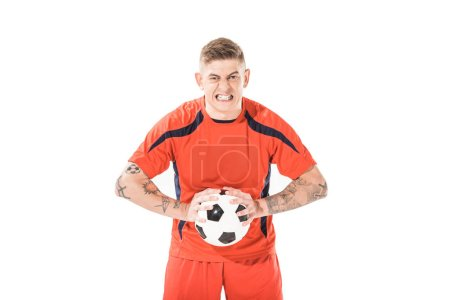 angry young soccer player holding ball and looking at camera isolated on white
