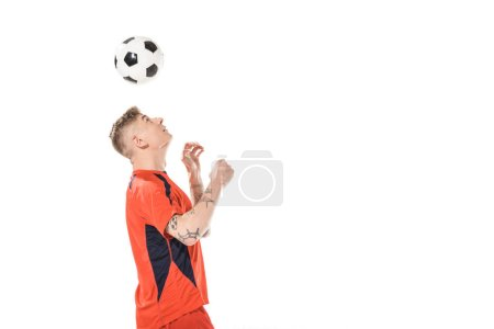 young soccer player hitting ball with head and looking up isolated on white