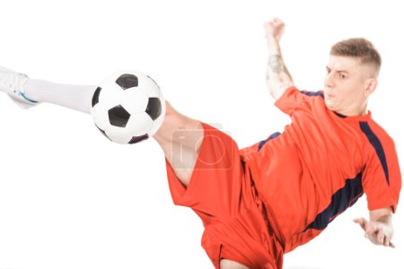 close-up view of young soccer player hitting ball with leg isolated on white