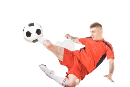 Photo for Young soccer player kicking ball in jump isolated on white - Royalty Free Image
