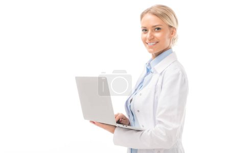 happy young female doctor working with laptop and looking at camera isolated on white