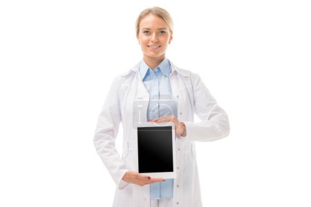 smiling young female doctor holding tablet with blank screen and looking at camera isolated on white