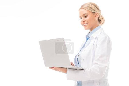 happy young female doctor working with laptop isolated on white