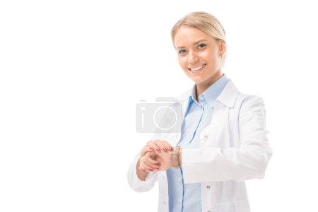smiling young female doctor checking time with wrist watch and looking at camera isolated on white