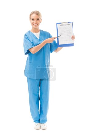 smiling young nurse pointing at clipboard with insurance form isolated on white