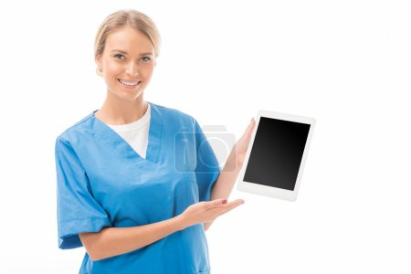 smiling young nurse pointing at tablet with blank screen isolated on white