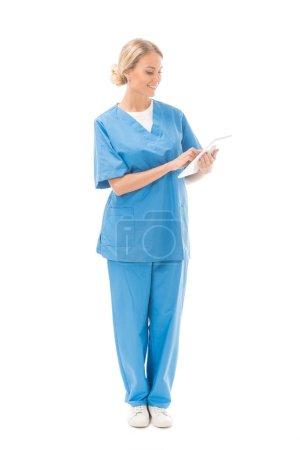 glückliche junge Krankenschwester arbeitet mit digitalem Tablet isoliert auf weiß