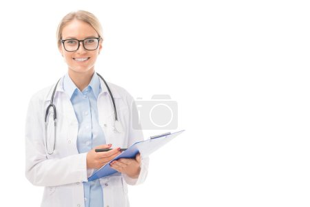 Photo for Confident young female doctor with clipboard looking at camera isolated on white - Royalty Free Image
