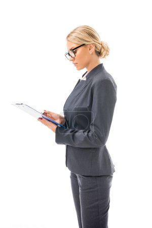 confident young businesswoman writing in clipboard isolated on white