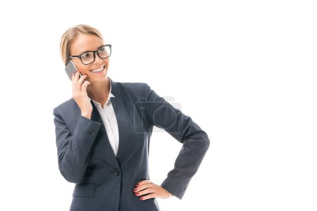 smiling young businesswoman talking by phone and looking away isolated on white