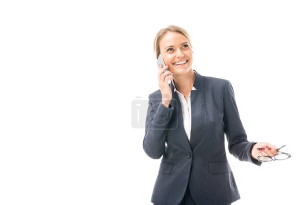 smiling young businesswoman talking by phone and looking up isolated on white
