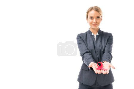smiling young businesswoman holding aids awareness red ribbon symbol isolated on white