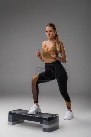 sportive young woman working out on step aerobics board on grey