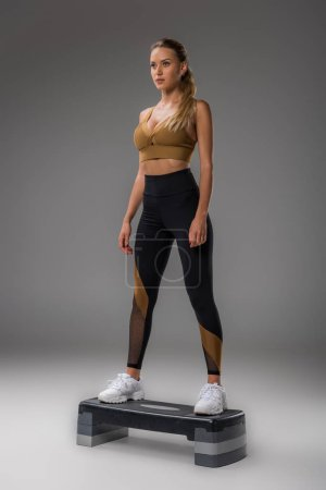Photo for Attractive young woman doing step aerobics on grey - Royalty Free Image