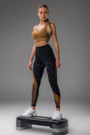 Photo for Fit young woman doing step aerobics on grey - Royalty Free Image