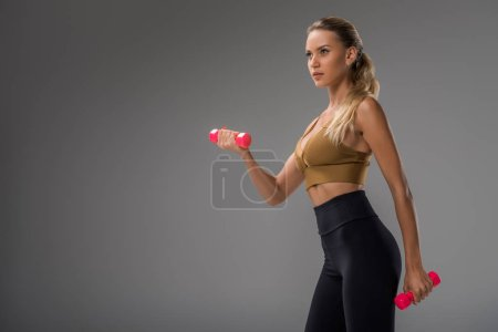 Photo for Athletic young woman exercising with dumbbells on grey - Royalty Free Image