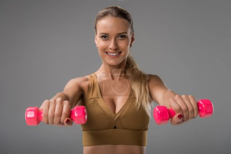 close-up portrait of sportive happy young woman exercising with dumbbells on grey
