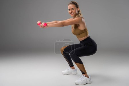 athletic smiling young woman doing squats with dumbbells on grey