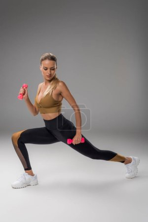 athletic young woman doing lunge with dumbbells on grey