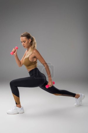 sportive young woman doing lunge with dumbbells on grey