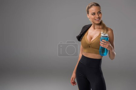 sportive young woman with towel and fitness water bottle standing on grey