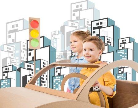 Photo pour Heureux frères et sœurs jouer avec voiture en carton et feux de circulation dans la ville dessinée - image libre de droit