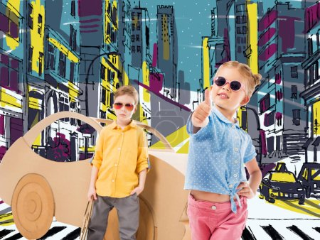 adorable stylish child in sunglasses showing thumb up while boy standing near cardboard car in drawn city