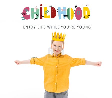"Photo for Happy boy in yellow crown with outstretched hands isolated on white with ""childhood - enjoy life while you are young"" lettering - Royalty Free Image"