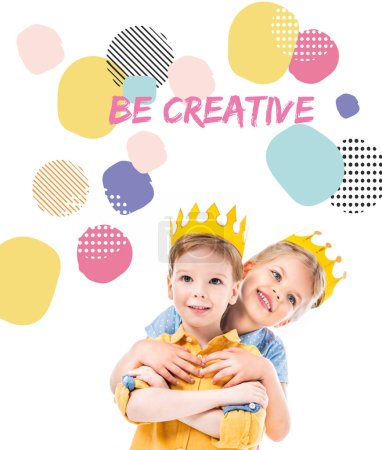 """sister hugging brother, kids in yellow paper crowns, isolated on white with """"be creative"""" inspiration"""