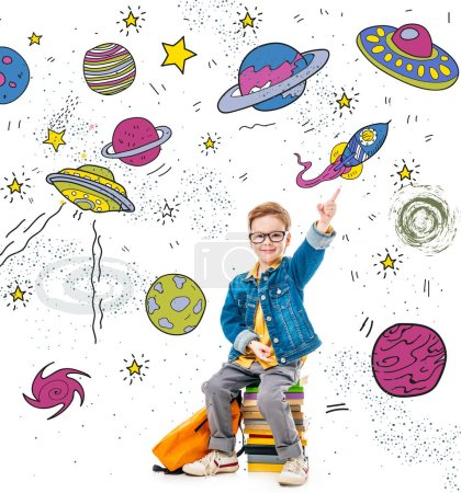 smiling schoolboy pointing up while sitting on pile of books with backpack, isolated on white with fantasy universe, planets and spaceships
