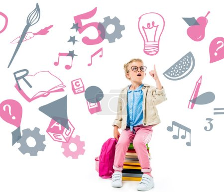excited schoolchild pointing up and having idea while sitting on pile of books with backpack isolated on white with study icons