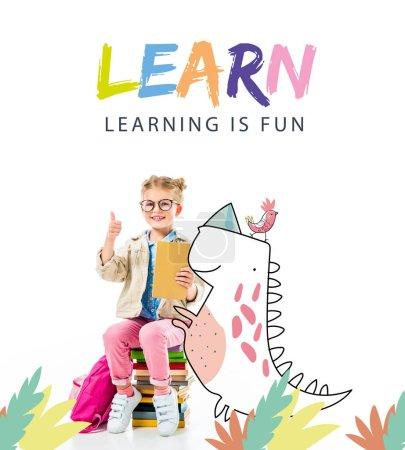 """Photo pour Adorable élève souriant montrant pouce levé tout en étant assis sur une pile de livres avec dinosaure imaginaire isolé sur blanc avec lettrage """"apprendre - apprendre est amusant"""" - image libre de droit"""