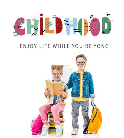 "schoolchildren in eyeglasses studying and sitting on books with backpacks, isolated on white with ""childhood - enjoy life while you are young"" lettering"