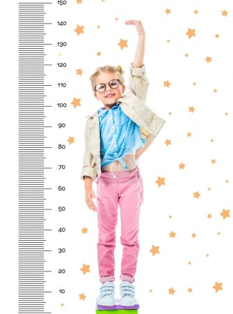 happy kid in eyeglasses standing on pile of books to be higher isolated on white with stars and growth measures