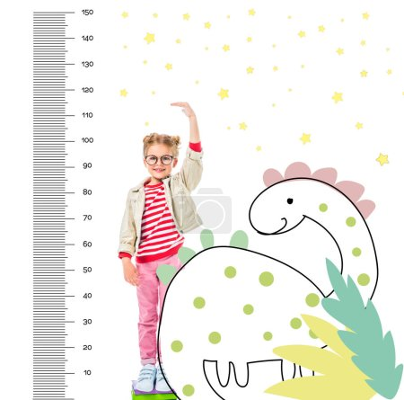 Photo pour Enfant souriant debout sur un tas de livres pour être plus isolé sur blanc avec des mesures imaginaires de dinosaure et de croissance - image libre de droit