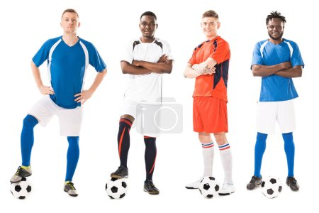 confident young multiethnic soccer players standing with balls and looking at camera isolated on white