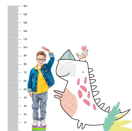 boy standing on pile of books to be higher, isolated on white with imaginary dinosaur and growth measures
