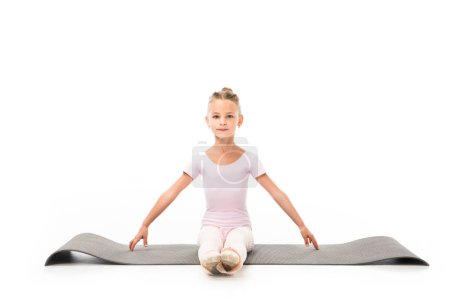 child practicing gymnastics exercises on fitness mat isolated on white background