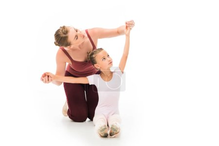 adult female trainer helping little kid exercising isolated on white background