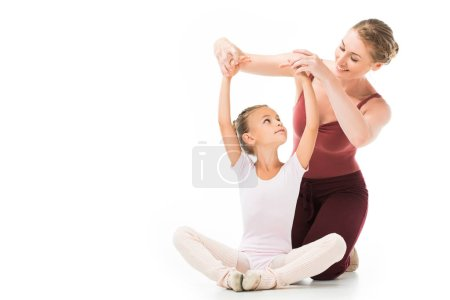 smiling female trainer helping little kid exercising isolated on white background