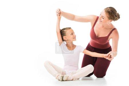 happy female trainer helping little kid exercising isolated on white background