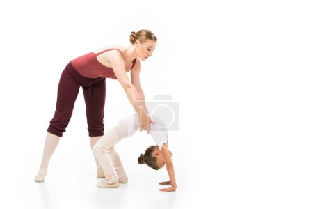 Photo for Female trainer holding little kid while she doing gymnastics bridge isolated on white background - Royalty Free Image