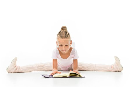 concentrated little ballerina reading book and doing twine isolated on white background