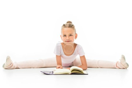 smiling little ballerina reading book and doing twine isolated on white background