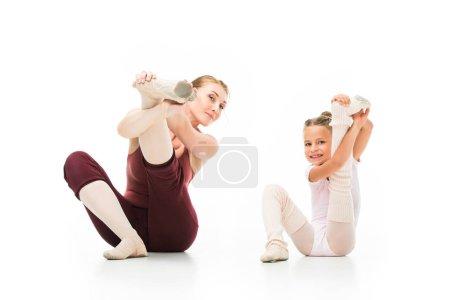 Photo pour Bonne petite ballerine et son entraîneur féminin qui s'étend de jambes isolés sur fond blanc - image libre de droit