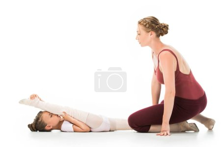 side view of adult female trainer helping little kid stretching isolated on white background