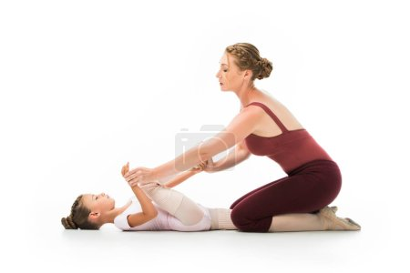 confident female trainer helping little ballerina stretching isolated on white background